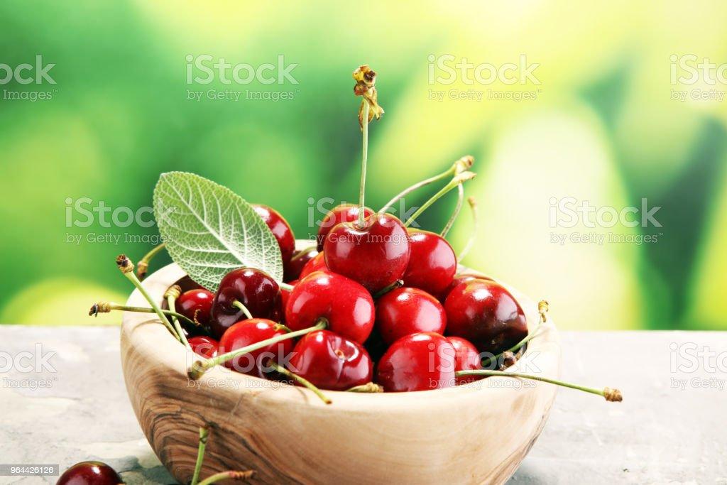 Kers. Rode verse kersen in kom en een bos van kersen op tafel - Royalty-free Bes Stockfoto