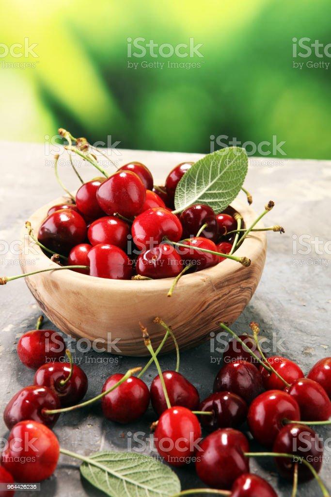 Cereja. Cerejas frescas vermelhas na tigela e um monte de cerejas em cima da mesa - Foto de stock de Alemanha royalty-free