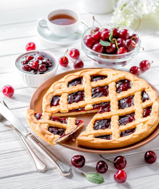 kirsch torte auf weißem holz hintergrund serviert mit frischen beeren - crostata stock-fotos und bilder