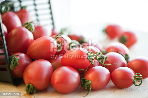 wet red cherry tomatoes in plastic basket on wooden background