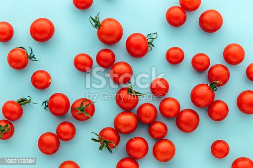 Colorful organic cherry tomatoes on a blue background, Marble Red Holland cherry tomato