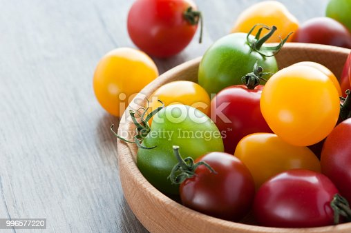 multi colored cherry tomatoes in wooden plate on wooden background