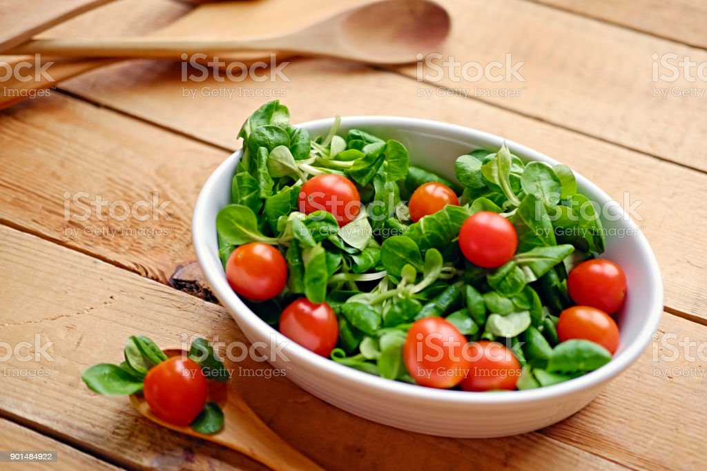 Cherry tomatoes and basil salad on a plate with a pot on a woode stock photo