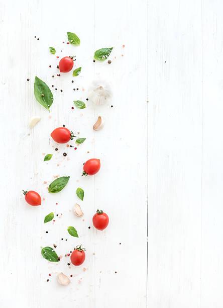 cherry-tomaten, knoblauch und frischem basilikum, nelken und gewürze auf - tropfenblatt tisch stock-fotos und bilder