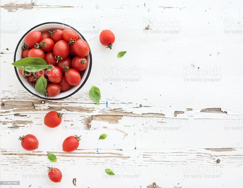 Cherry tomatoes in metal bowl and fresh basil leaves on stock photo