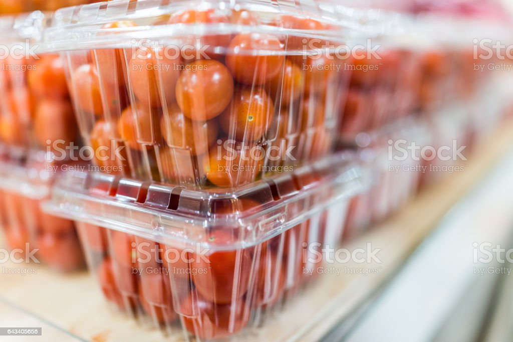 Cherry tomatoes in plastic boxes on display stock photo