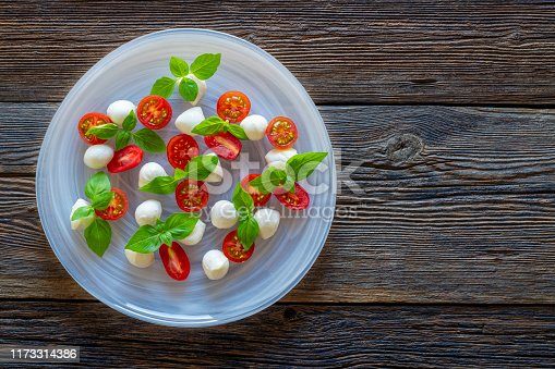 cherry tomatoes mozzarella and basil salad on wooden table
