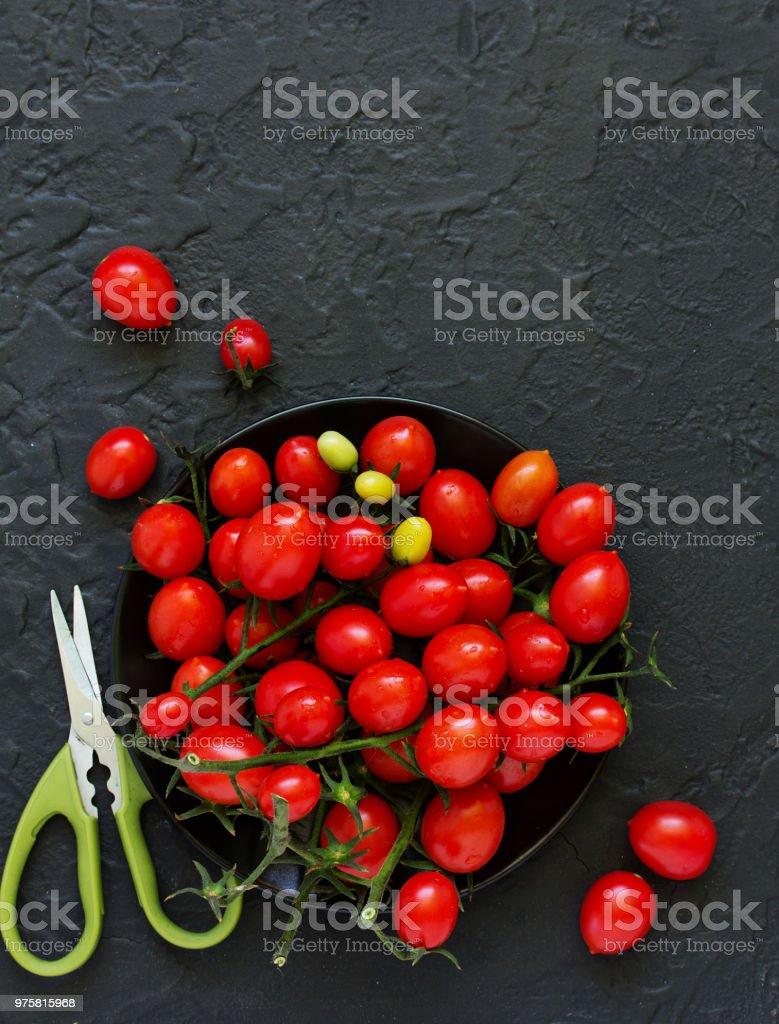 Cherry-Tomaten auf einem dunklen Hintergrund. Ansicht von oben. - Lizenzfrei Blatt - Pflanzenbestandteile Stock-Foto