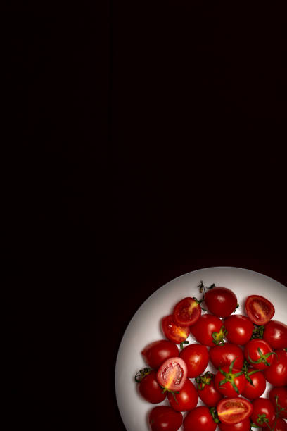 Cherry tomatoes on a white plate on a black background, top view stock photo