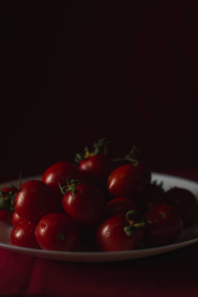 Cherry tomatoes on a white plate, shallow depth of field, dark dramatic effect stock photo