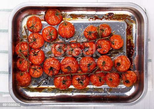 istock Cherry tomatoes on the vine roasted with herbs and balsamic vinegar. Top view. 691566920