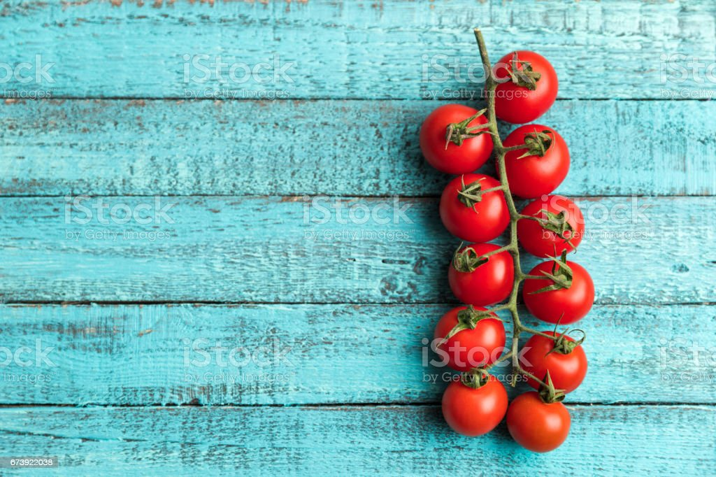 cherry tomatoes on turquoise wooden table top texture. fresh seasonal vegetables concept photo libre de droits
