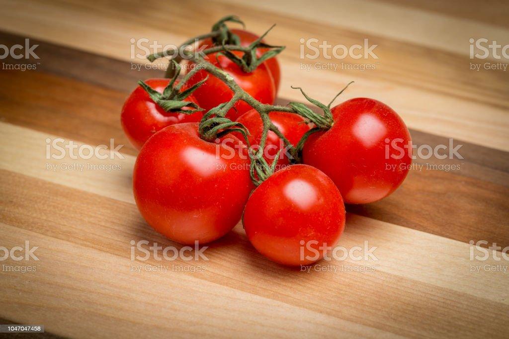 Tomates cerises sur planche à découper en bois - Photo