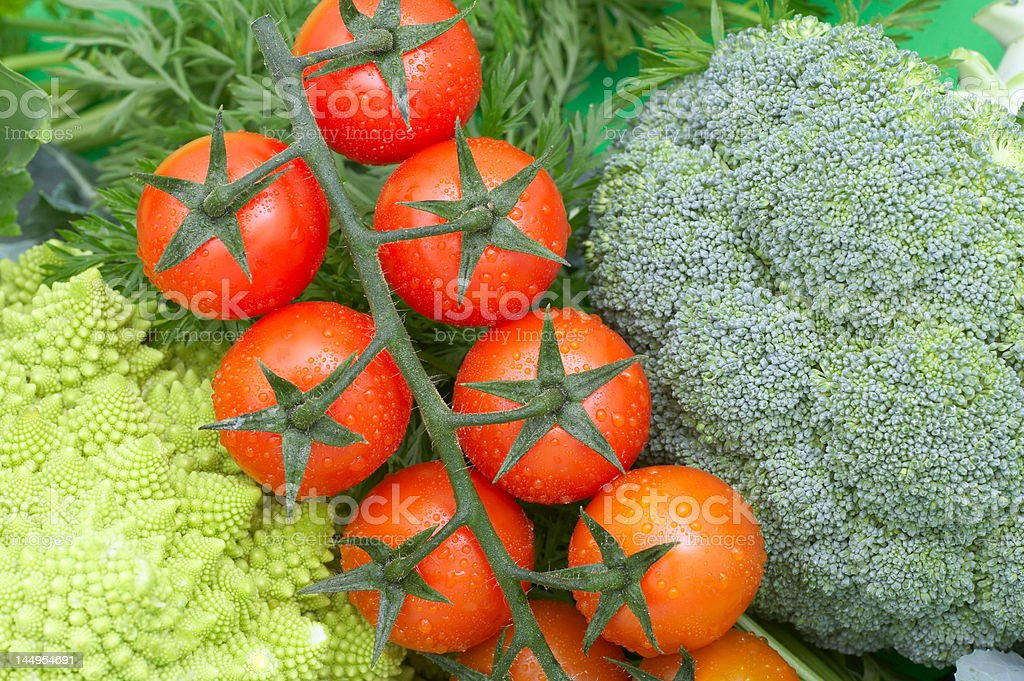 cherry tomatoes with broccoli and cauliflower as background royalty-free stock photo