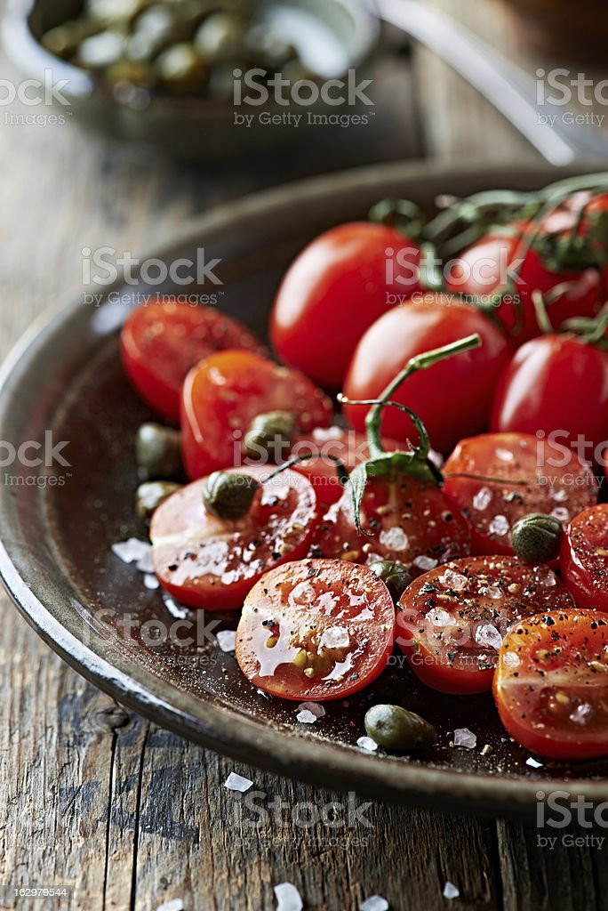 Cherry tomatoes with capers, sea salt and black pepper royalty-free stock photo