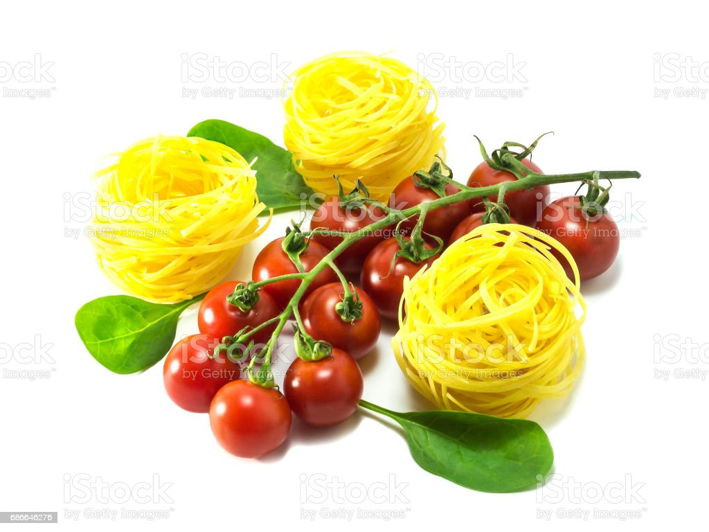 Cherry tomatoes with dry Italian pasta on a white background. royalty-free stock photo