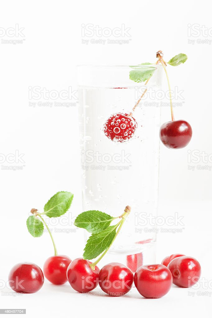 Cherry with bubbles in the glass of water stock photo