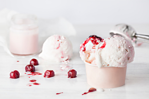 Cherry yogurt Ice Cream in a paper cup with cherries