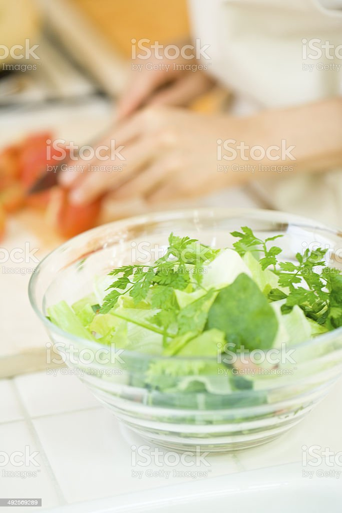 Chervil Herb salad and woman cutting tomato royalty-free stock photo