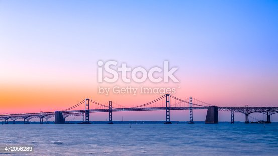 A beautiful sunrise over the calm waters under the Chesapeake Bay Bridge. The steel and concrete cantilever and suspension bridge near Baltimore, MD, stretches across the Chesapeake Bay.