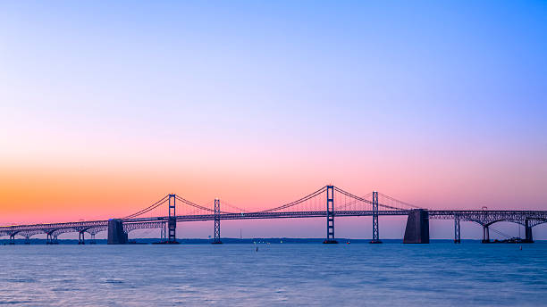 Chesapeake Bay Bridge with Beautiful Sunrise A beautiful sunrise over the calm waters under the Chesapeake Bay Bridge. The steel and concrete cantilever and suspension bridge near Baltimore, MD, stretches across the Chesapeake Bay. baltimore maryland stock pictures, royalty-free photos & images