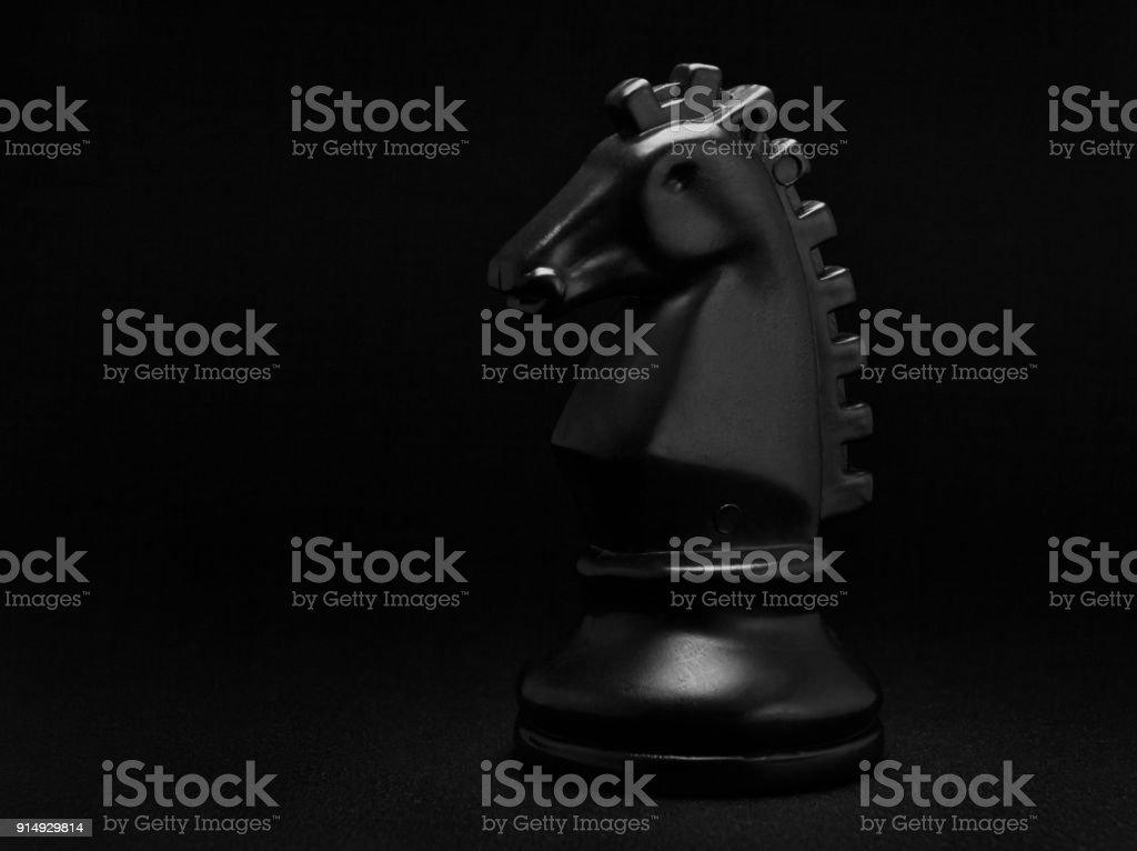 Chess. Black Knight on black background. stock photo