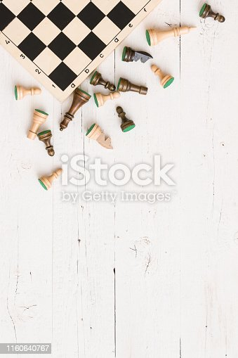 istock Chess board and chess figures on white wooden background. 1160640767
