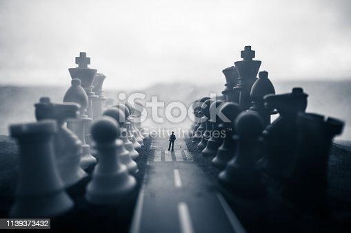 Chess concept of business and strategy ideas. Silhouette of a man standing in the middle of the road with giant chess figures. Little businessman on the road to success or troubles. Artwork decoration