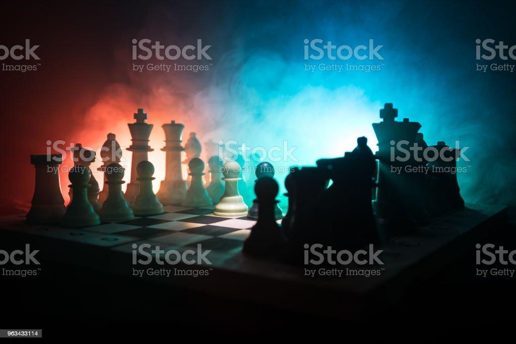Koncepcja gry szachowej pomysłów biznesowych i pomysłów na konkurencję i strategię concep. Figury szachowe na ciemnym tle z dymem i mgłą. Przywództwo biznesowe i koncepcja zaufania. - Zbiór zdjęć royalty-free (Biznes)