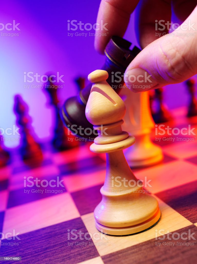 Chess bishop on a board with coloured lighting.