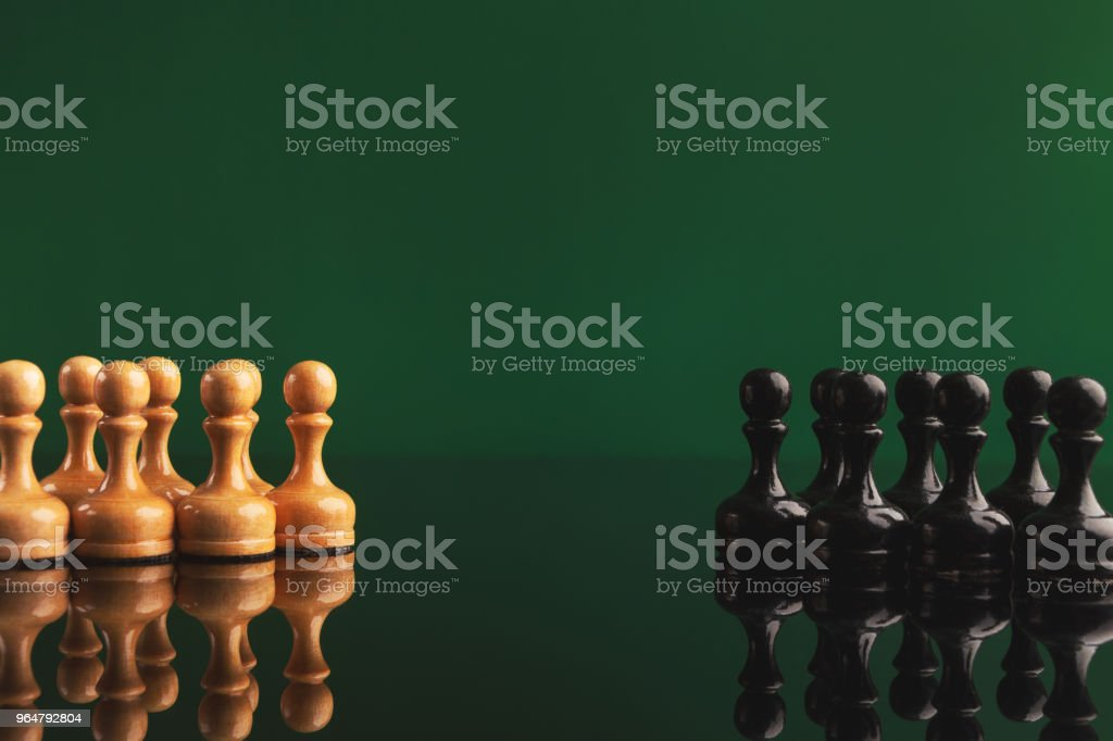 Chess figures on green background with reflection royalty-free stock photo