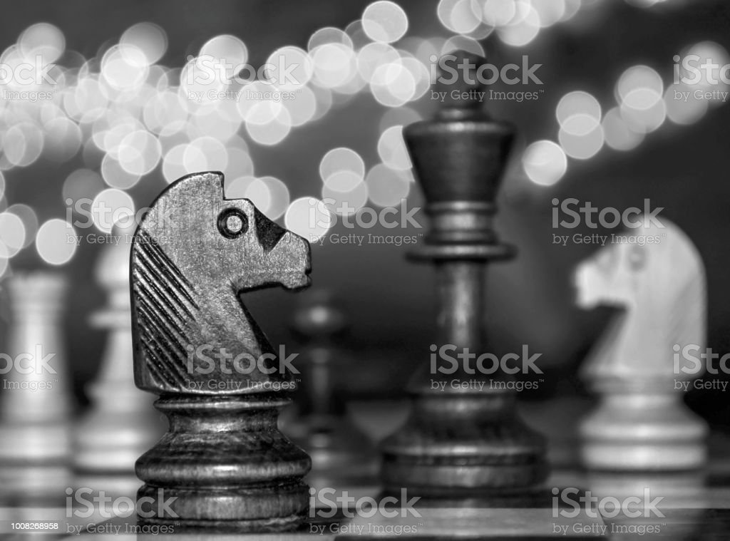 Chess horses and king on festive lighting background stock photo