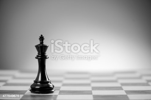 Classic wood chess board. The black king faces is all alone.