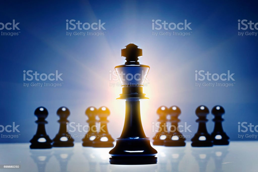 Chess king with defocused pawns in glowing blue light stock photo