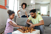 Father and Daughter Enjoy Playing Chess at Home in the Livingroom. Family Spend Time Happiness Holiday Togetherness. Family and Leisure Concept