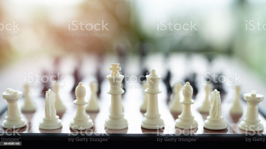 Chess on a Board of wood. bokeh nature background.  game, strategy, management or leadership concept royalty-free stock photo