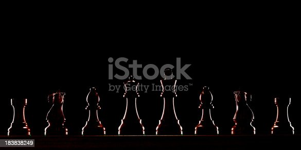 Black chess pieces lined up in the dark.See all my
