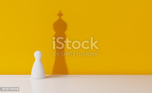 istock Chess Pawn Casting The Shadow Of A King Over Yellow Background 913175416