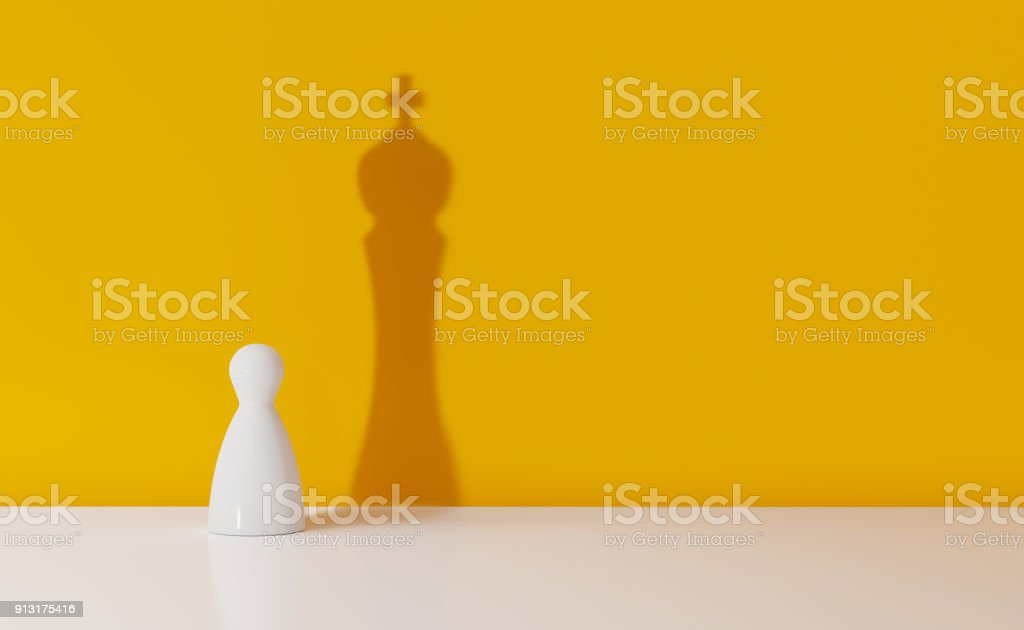 Chess Pawn Casting The Shadow Of A King Over Yellow Background stock photo