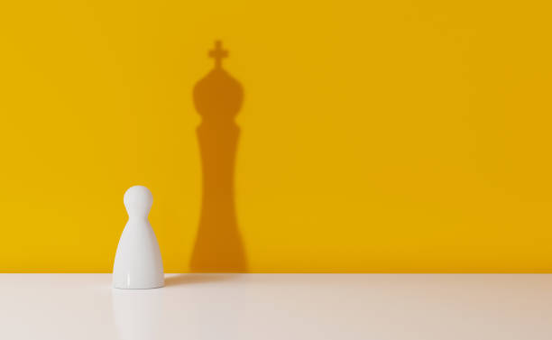 chess pawn casting the shadow of a king over yellow background - changing form stock pictures, royalty-free photos & images