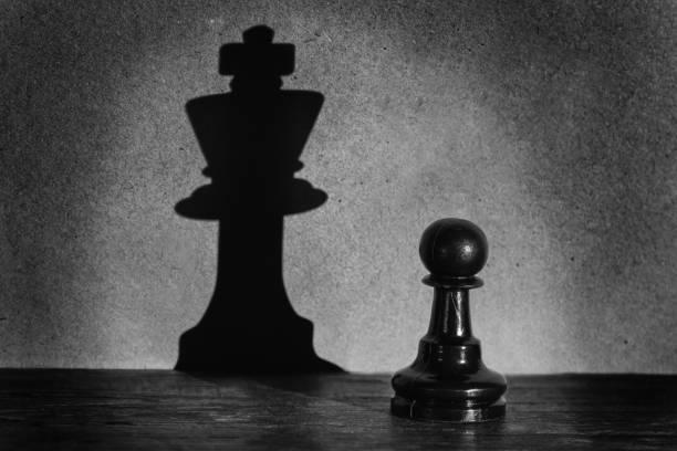 schach bauer stehen in einem scheinwerfer, die einen schatten des königs mit dunkelheit actistic konvertierung machen - könig stock-fotos und bilder