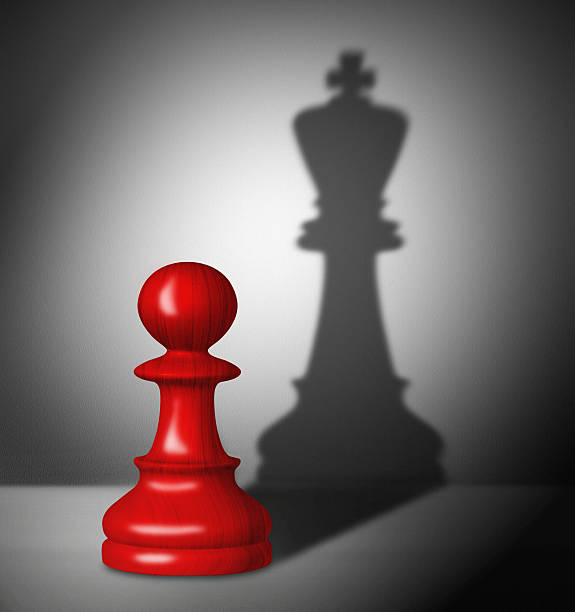 Chess pawn with the shadow of a king. stock photo