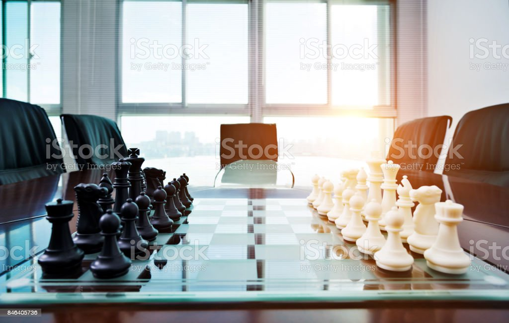 Chess pieces and board on the conference table stock photo