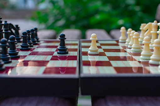 Chess pieces are placed on a chessboard on a blurred background of nature. The pawns are black and white opposite each other. Blurred focus. Defocus. Shehamat day