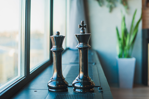 Chess pieces, black king and queen, large pieces stand on a black windowsill near the window