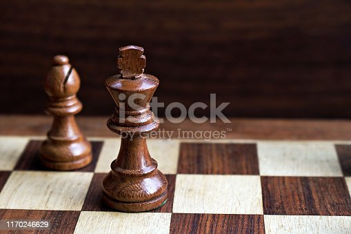 Brown King And Bishop Chess piece game figures stock photo over a wooden chess board on black background. Depth of field in object photography. The chess pieces are made up of wood or wooden and has single cut piece crafted, carved, carving pieces, without any joint, no joints. The chess pieces are shiny or glossy brown in color colour coloured coloured. Conceptual photograph of a black bishop providing support to royal king.  No text. No people. Copy space. The chessboard is in beige or off white or light brown and dark brown contrast checks. The king stands tall on the brown square.