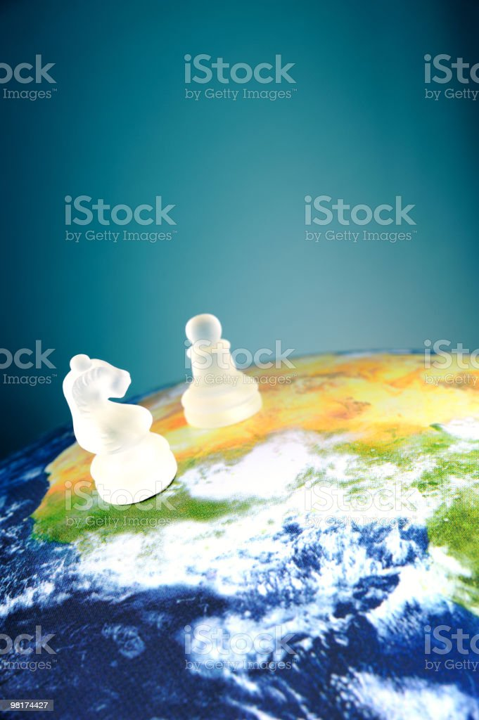 Chess pieces on planet Earth royalty-free stock photo