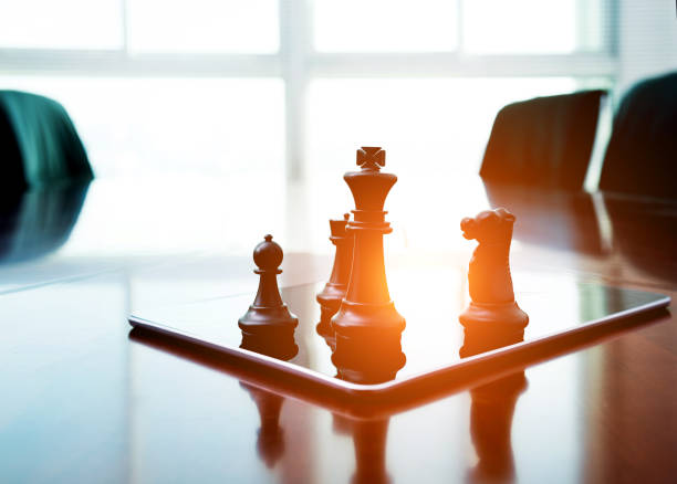 Chess pieces standing on the digital tablet stock photo