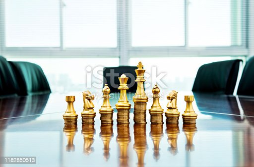 Chess pieces standing on the stacked coins.