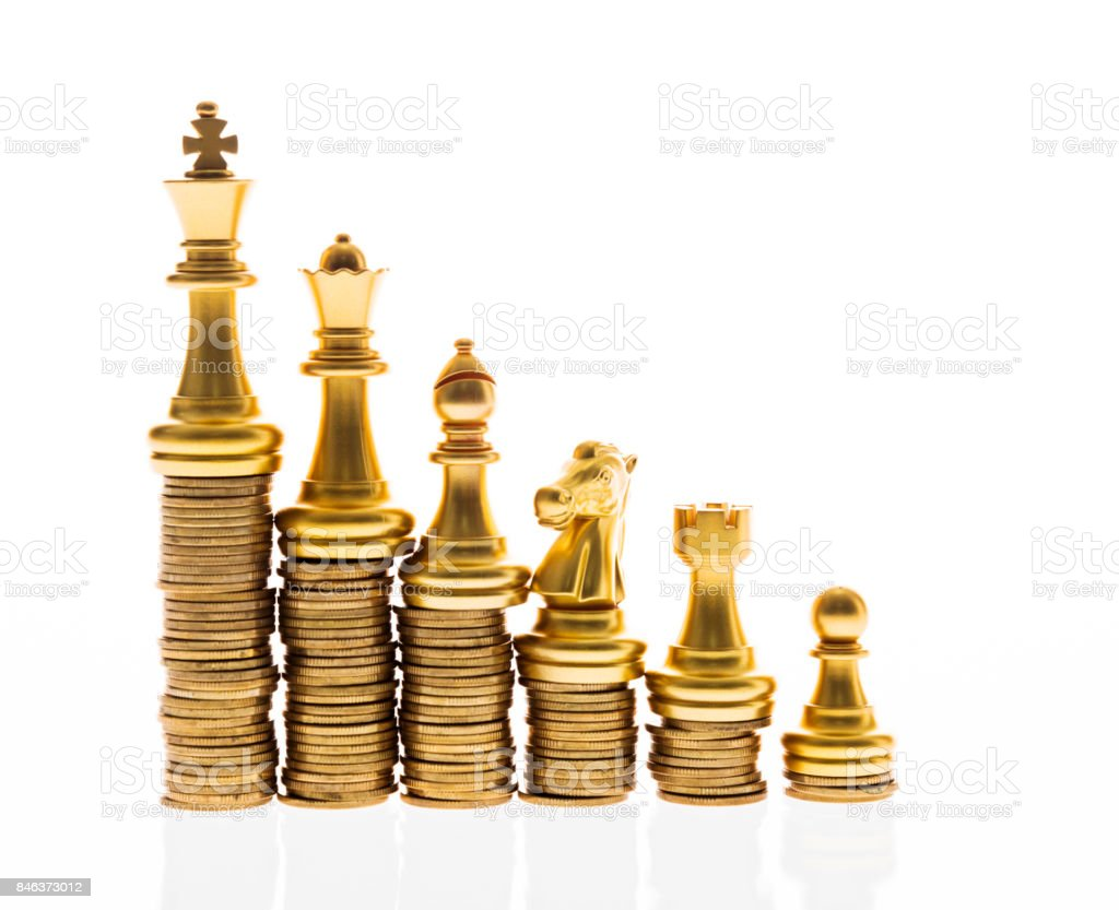 Chess pieces standing on the stacked coins stock photo